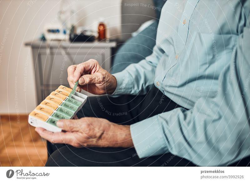 Senior man patient opening pill dispenser to take next medicine dose. Organising medication person hospital senior medical illness nurse sick care clinic