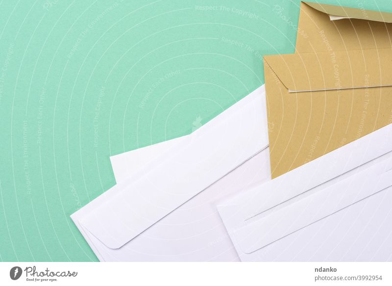 blank white paper brown and white envelopes on a green background letter empty message office post card document mail postage stationery delivery communication