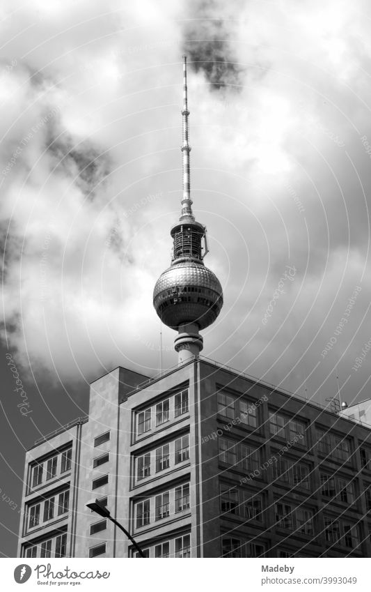 The Berlin TV tower behind a cubic office building with clouds in sunshine at Alexanderplatz in the capital Berlin, photographed in classic black and white