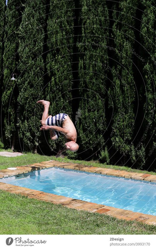 A man is jumping into the pool somersault. Upside down, jump into the water. falling swimming male vacation sunglasses shirtless bald swimsuit poolside leisure