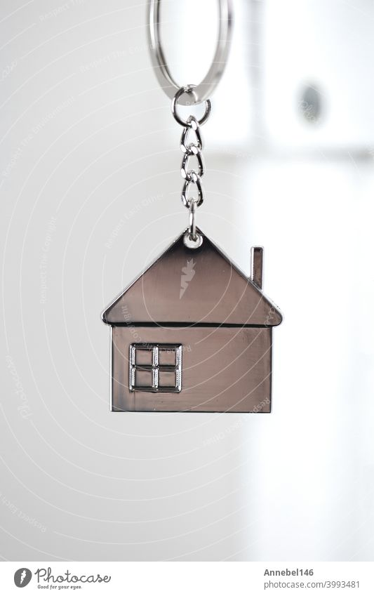 Silver house key in white door, with little keychain house, opening door to new house, home, investment, real estate concept, space for text security metal lock