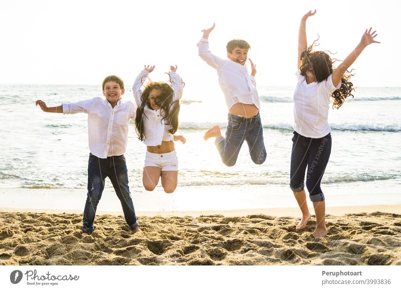 Happy kids jumping together on the beach children sea people family water summer sky sunlight happy group sunset vacation travel joy boy girl holiday fun young