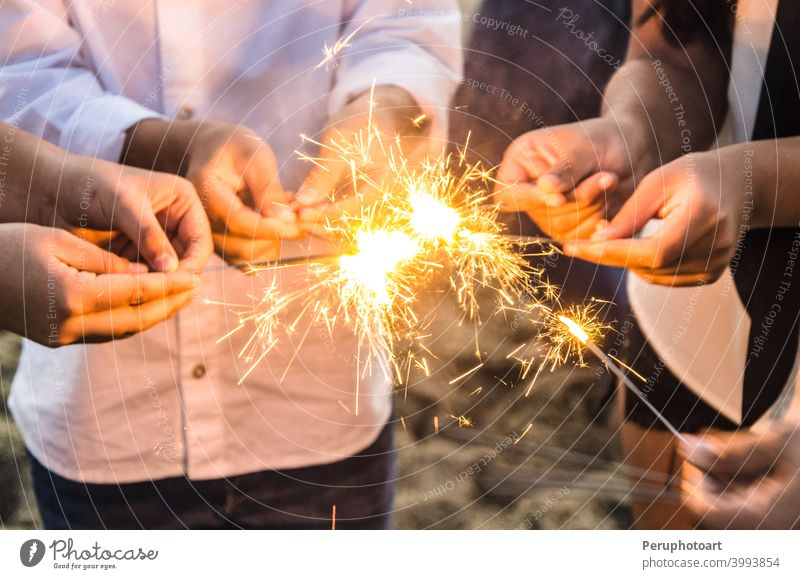 Beautiful sparklers in people hands, xmas and new year concept. light background celebration evening holding night fireworks abstract beautiful birthday