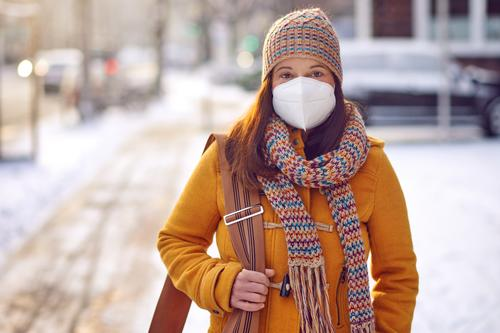 Middle-aged brunette woman in winter clothes wearing face mask outdoors due to Corona virus outdoors while on her way to work middle-aged ffp2 protection safety