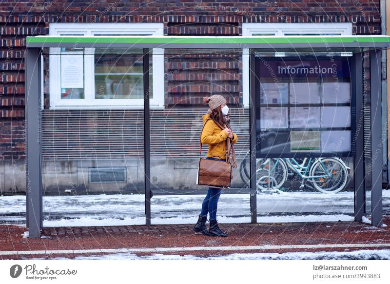 Midde-aged brunette woman standing at a bus stop, wearing a protective face mask due to corona virus, waiting for her bus to bring her to work middle-aged