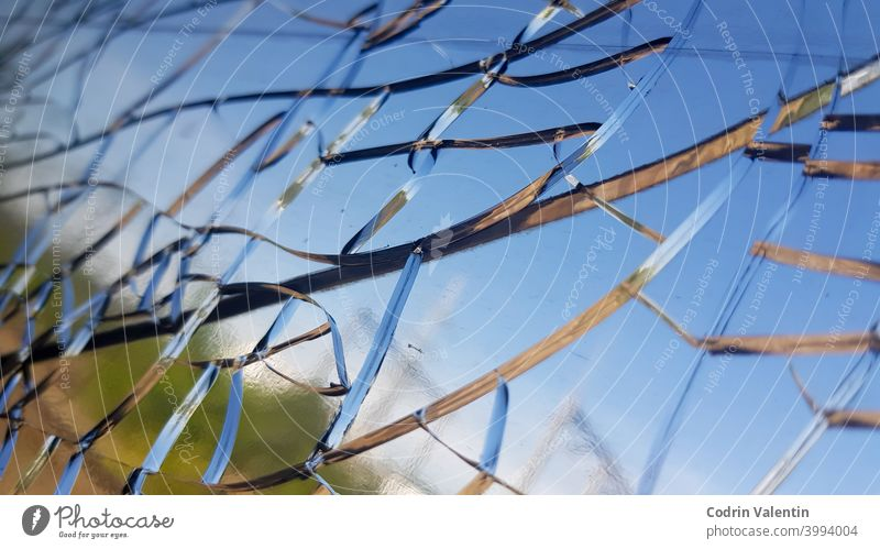 Closeup shot of the cracks on the glass of a window abstract blue sky blur broken crash damage design impact landscape light nature no person outdoor outdoors