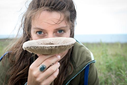Young woman holding a big lame mushroom and looking at the camera Nature Summer daylight Day Sky Flourish wax slats Mushroom Meadow blades of grass Grass Plant