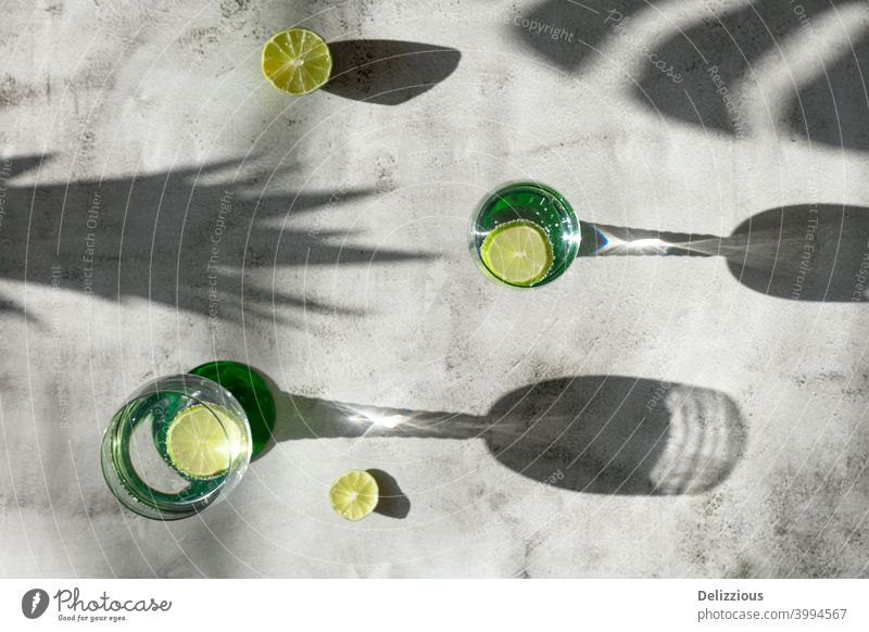 top down view of drinks and shadows with lime, tropical mood on light surface water ingredient white background citrus closeup cocktail cold concept copy space