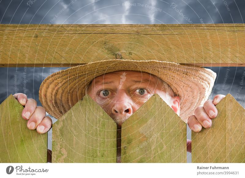A curious man peers over a garden fence. He is wearing a straw hat. Thunderclouds can be seen in the background. Man Neighbor Curiosity inquisitorial Spy