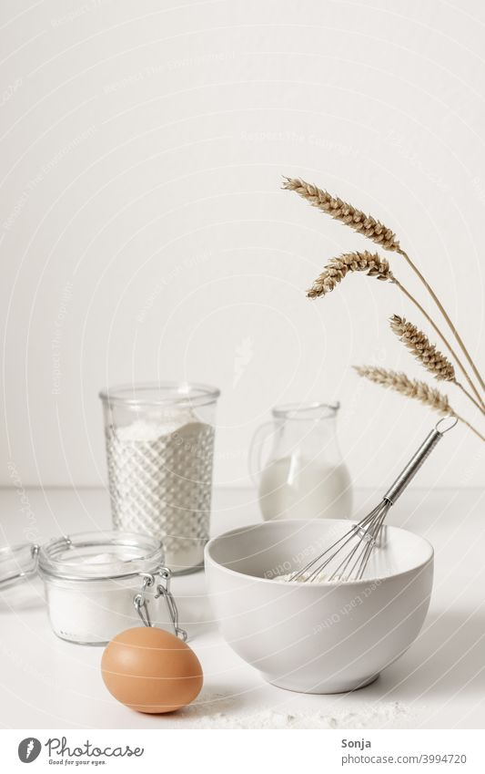 flour in a bowl and baking ingredients on a white table Flour Ingredients Baking Egg Table white background Wheat ear Kitchen Preparation Raw Cooking Fresh