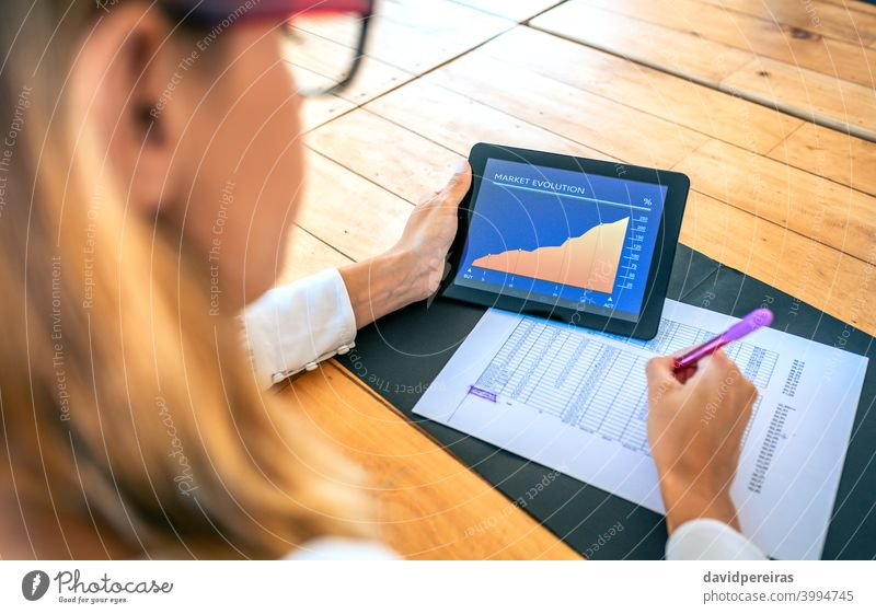 Businesswoman analyzing market evolution with tablet businesswoman investor success analyze documents alternative investment screen working unrecognizable