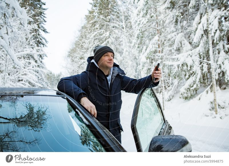 Man in warm winter clothes standing at the car, using phone. Snowy winter country road, car covered with ice, Beautiful forest under the snow. help call