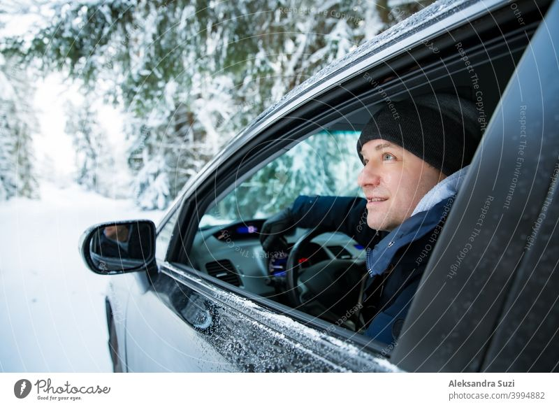 Man in warm winter clothes sitting in car. Snowy winter country road, car covered with ice, Beautiful forest under the snow. auto blizzard cold commute