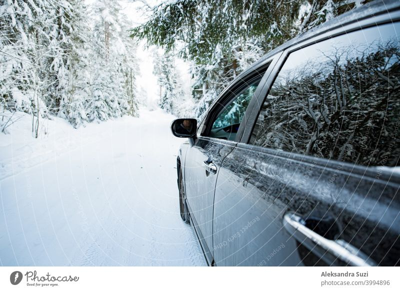 Car covered with snow and ice driving on the winter road. Beautiful landscape of winter forest and snowy country side. auto automobile blizzard car christmas