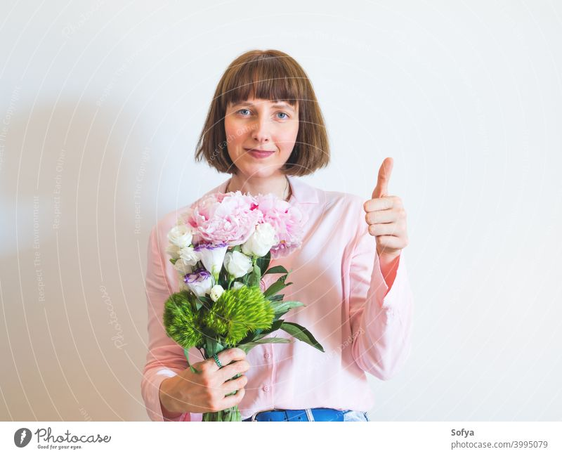 Woman in pink holding beautiful bouquet with hand thumbs up woman approve yes support local shopping mother day mothers day flowers spring face lifestyle