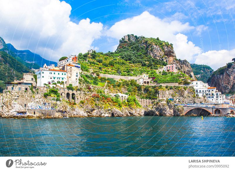 Panoramic view, aerial skyline of small haven of Amalfi village with tiny beach and colorful houses located on rock. Tops of mountains on Amalfi coast, Salerno, Campania, Italy