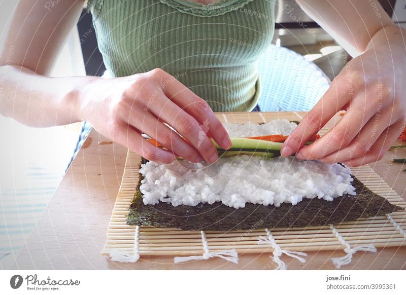 Hands of a woman preparing sushi by herself hands Upper body Sushi Eating preparation Kitchen Rice Salmon Japanese Asian Food traditionally Wasabi Ginger