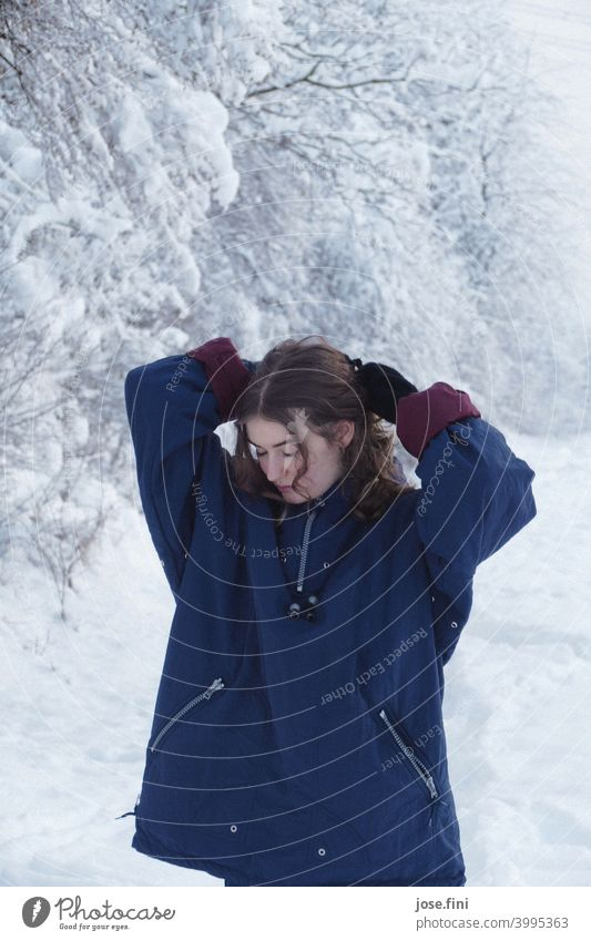 Young woman with warm clothes, looking down, hands above her head, snow in the background. one person young adult Girl Youth (Young adults) Feminine portrait
