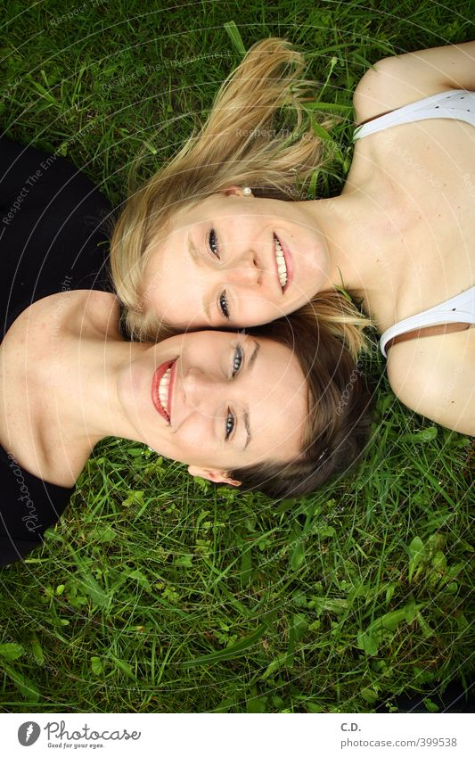 Lia & Kira Feminine Friendship Head 2 Human being Summer Grass Smiling Lie Happiness Joy Together Colour photo Exterior shot Day Looking into the camera