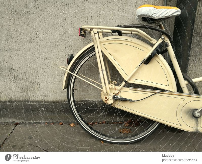 Classic Holland bike in beige with saddle cover in front of a matching house wall in Cologne on the Rhine in North Rhine-Westphalia Wheel Bicycle hollandrad