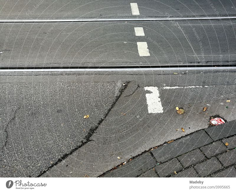 Old grey asphalt with tram tracks and white markings of a pedestrian crossing in Cologne on the Rhine in North Rhine-Westphalia, Germany Street Traffic lane