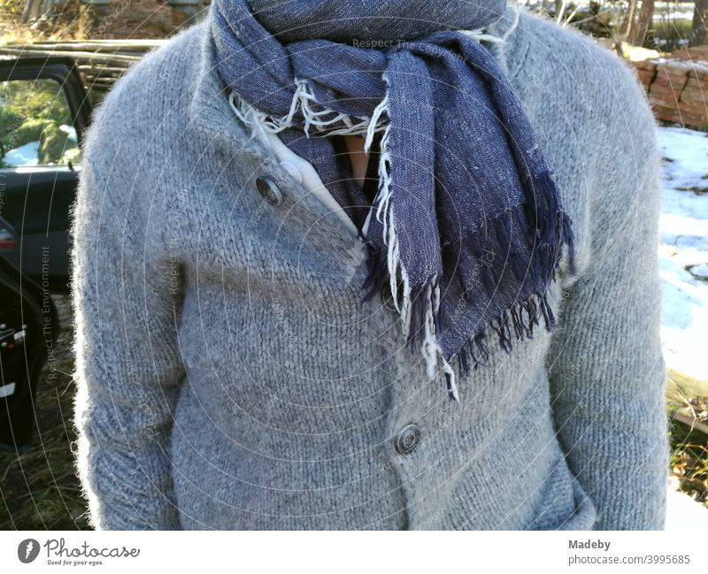 Rustic dressed woman with grey wool jacket and blue scarf with fringes in autumn in front of a farm in Rudersau near Rottenbuch in the district Weilheim-Schongau in Upper Bavaria