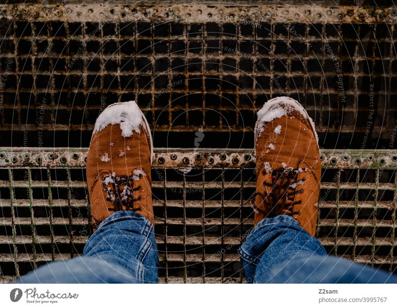 Winter boots with snow on stairs Winter walk Boots Snow Legs feet winter shoes Buckskin Leather Brown jeans Blue Stairs men's shoes Man Bird's-eye view Fashion