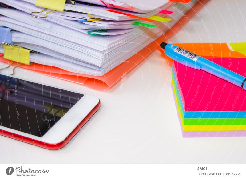 Close-up of a pile of paper with colored post its and a pen. Information overload concept information stress business datum white problem office computer