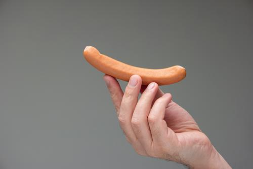 Caucasian male hand holding a bratwurst dog between fingers isolated on gray background man studio frankfurter delicious close-up nutrition warm grilling