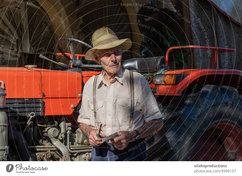 Old farmer working on red tractor under roof of farmhouse in sunshine. more adult aged Agriculture car automobile Car Caucasian Characters test Landscape