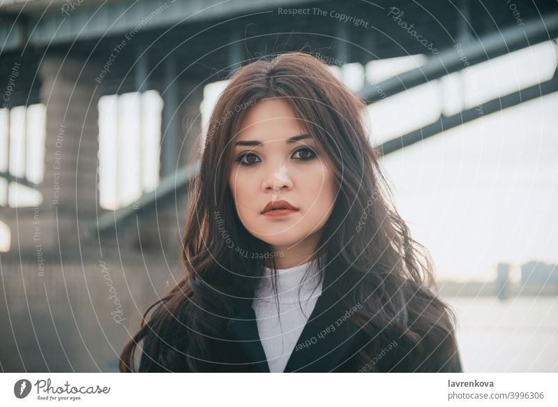 Portrait of asian woman in front of the bridge in cold fair weather girl female diversity portrait pretty coat hair outdoors alone autumn fall winter seasonal