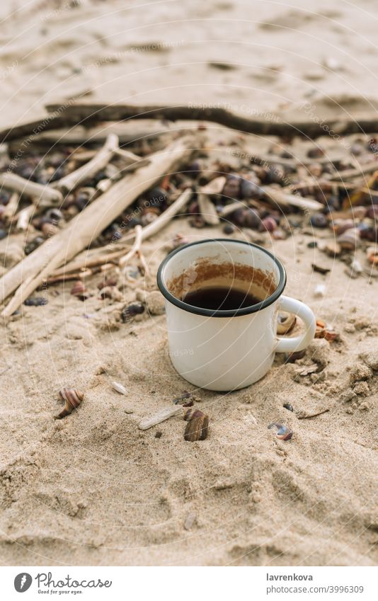 Enamel mug with hot drink standing in a sand on a wild beach cup enamel picnic autumn tea cold still life beverage metal getaway selective focus outdoors spring