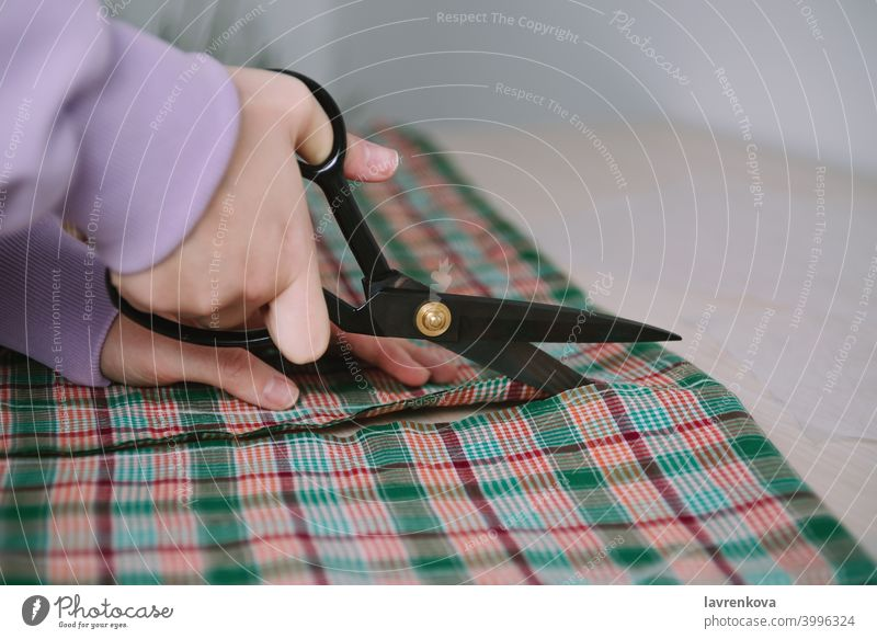 Closeup of woman hands holding scissors and cutting plaid fabric for sewing clothes seamstress textile cutting out occupation tailor workshop creative business