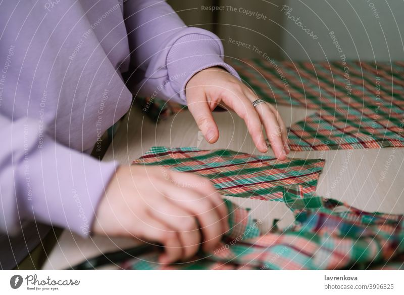Closeup of female tailor cuting out checkered fabric with a paper pattern to make out a shirt tailoring woman sewing plaid cutting clothing textile cut out