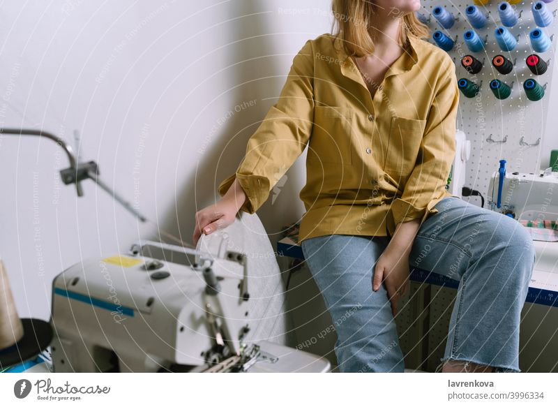Faceless shot of young female in yellow shirt sitting in her sewing workshop in front of the colorful threads woman seamstress machine textile tailor overlock