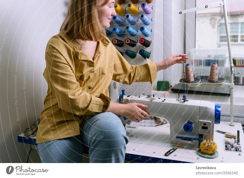 Young woman in yellow shirt sits in her sewing workshop in front of the colorful threads and the sewing machine Woman Sewer Machinery textile Tailor Overlock