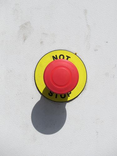 Emergency stop button in signal colours Signal alarm button Safety Exterior shot Light and shadow Symbols and metaphors Caution Round Pushing Red Yellow White