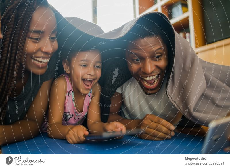 Family taking a selfie with phone. family mobile home lifestyle indoor mobile phone parenting relationship daddy cute mother daughter children at home