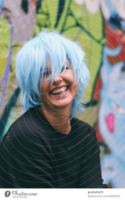 Portrait of a happy, laughing woman / artist with blue hair Looking into the camera Front view Upper body portrait Central perspective Shallow depth of field