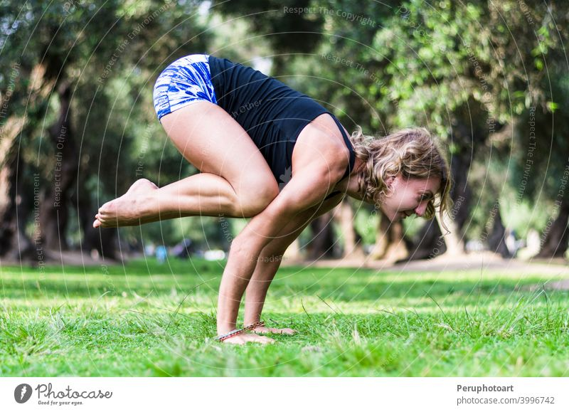Yoga in the park, middle age woman doing bakasana exercise crane pose. adult balance beautiful body caucasian concentration female fitness grass healthy