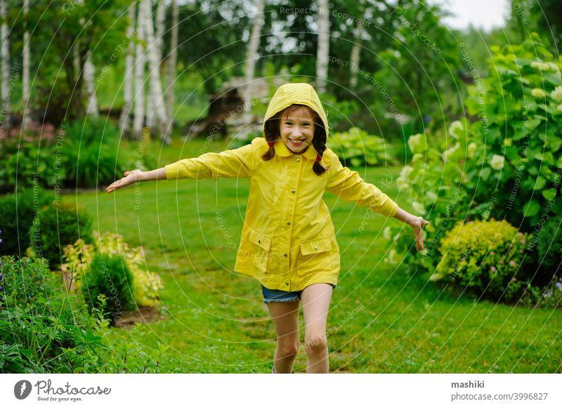happy kid girl in yellow raincoat playing and having fun in summer garden under the rain child outdoor weather boot rainy waterproof wet little nature childhood