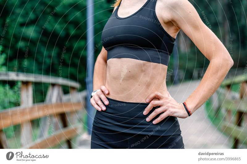 Athlete woman posing with sportswear sportswoman midsection top slender flat stomach abs unrecognizable healthy athlete training skin moles arms hands