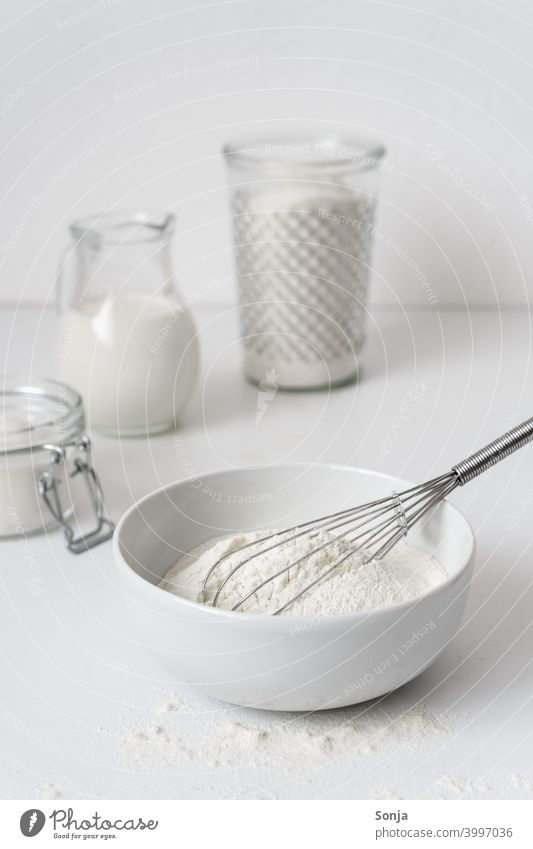 Flour in a bowl and ingredients on a white table Milk Sugar Breakfast bake a cake Table White Storage tank Glass Preparation dough Kitchen Baking Food