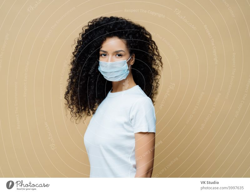 Sideways shot of Afro American woman wears protective face mask, protects against spread of coronavirus disease, stays at home, follows rules of self isolation. Covid-19, safety, quarantine concept