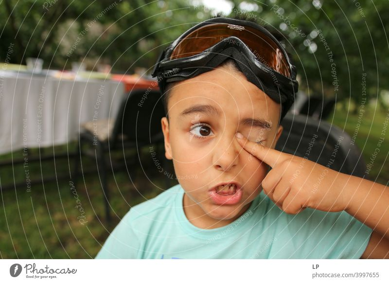 Child making a face and holding his finger on his eye hesitant puzzled Perplexed sceptical doubts doubtful Doubt hestitate uncertainty confusion Infancy reality