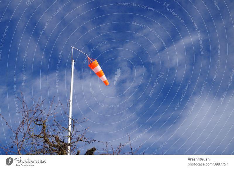 Waving windsock under blue sky Windsock Sky Blue Clouds Nature outside Orange-white Blow Warn Sign