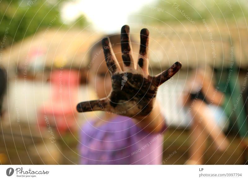 child showing a painted black palm Front view Portrait photograph Central perspective Blur Day Detail Close-up Pattern Unfriendly Black Skin color Fingers