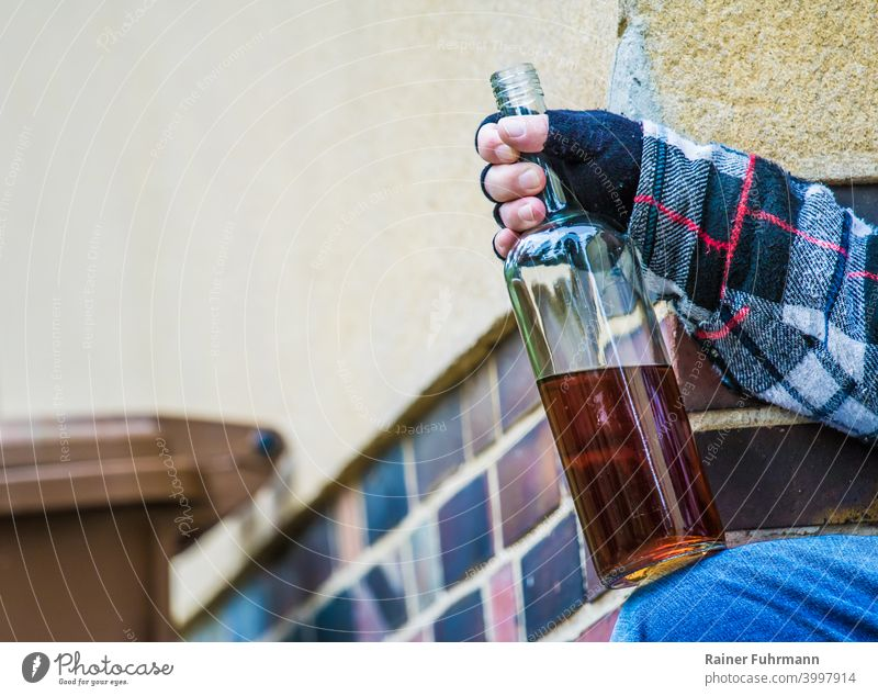 Close-up of an anonymous man sitting by a building and holding an open bottle of schnapps Alcoholic drinks alcoholism Addiction Building dustbin drunk Drinking