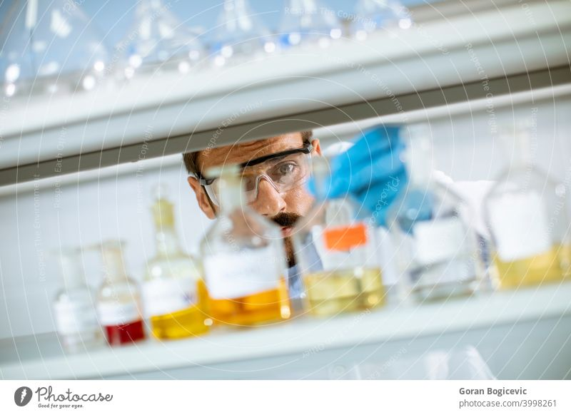 Young researcher with protective goggles checking test tubes analysis analyzing biochemist biochemistry biology biotechnology caucasian chemical development