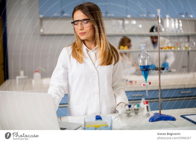 Female researcher in white lab coat and protective mask using laptop while working in the lab analyzing background bio chemical chemist clinic computer